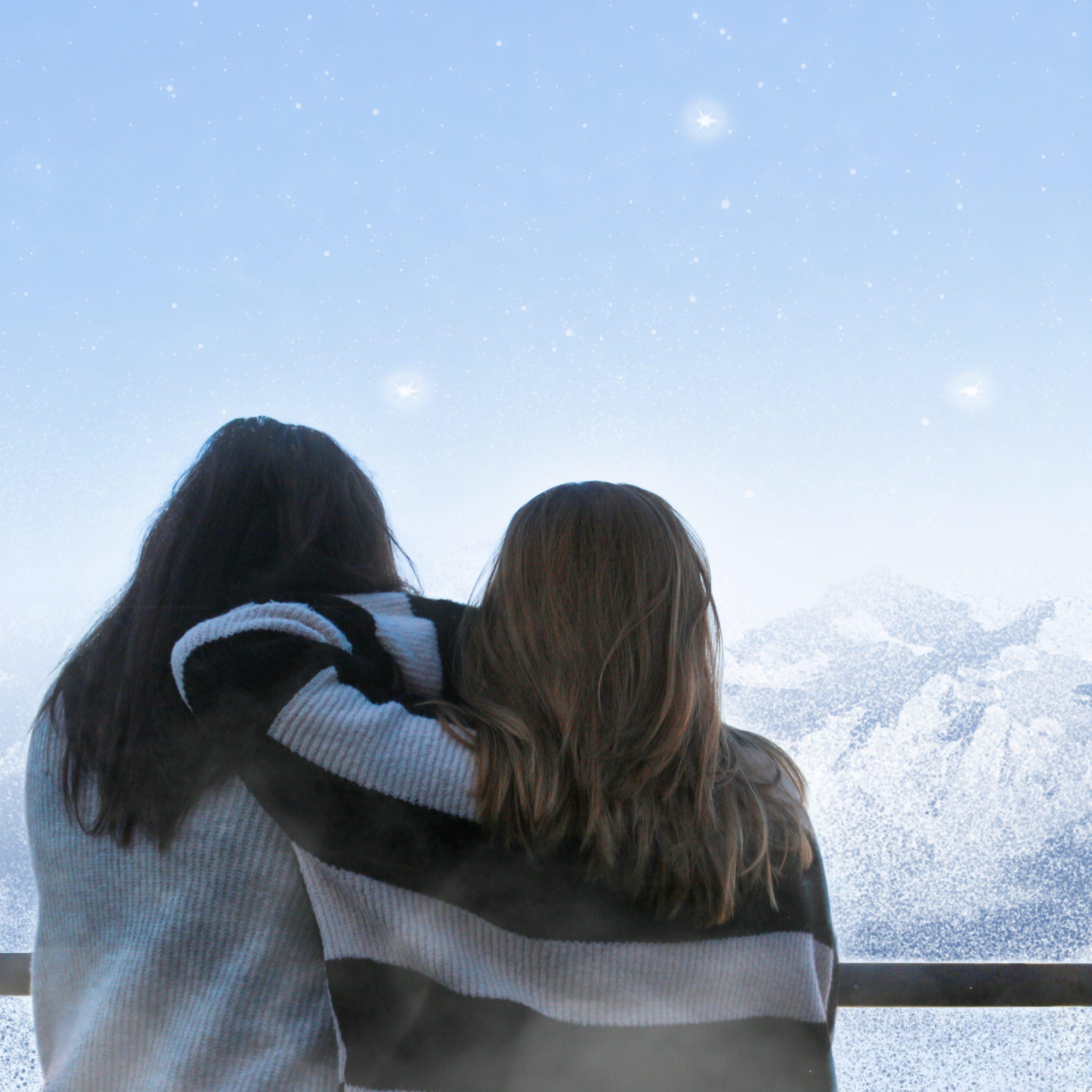 Foto de Laura y Cris con un cielo azul de fondo y unas montañas hechas que parecen magia