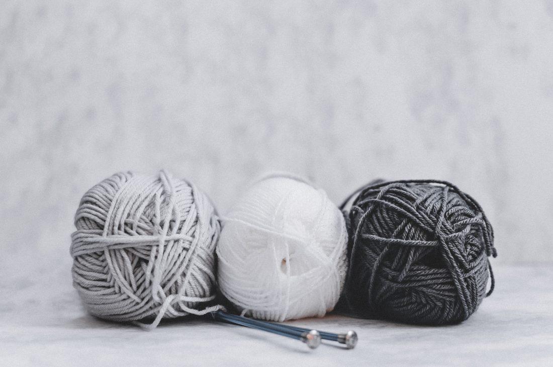 Tres ovillos de lana en color blanco, gris y negro sobre fondo blanco y con dos ajugas de hacer punto. El punch needling es uno de los hobbies y habilidades que quiero probar